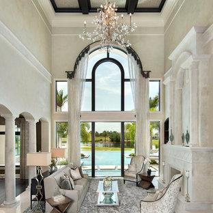 マイアミの巨大な地中海スタイルのおしゃれなLDK (フォーマル、ベージュの壁、大理石の床、標準型暖炉、石材の暖炉まわり、テレビなし、ベージュの床) の写真