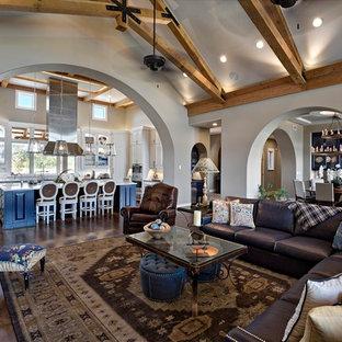 Diseño de salón abierto, clásico, grande, con paredes beige, suelo de madera oscura, chimenea de doble cara, marco de chimenea de piedra y televisor colgado en la pared