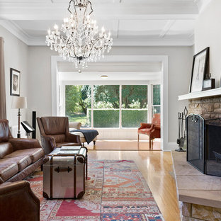 Photo of a mid-sized country formal living room in Wollongong with grey walls, light hardwood floors, a standard fireplace, no tv and beige floor.