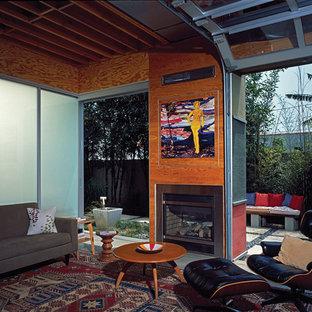 ロサンゼルスの小さいビーチスタイルのおしゃれなリビング (据え置き型テレビ、コンクリートの床、両方向型暖炉、金属の暖炉まわり) の写真