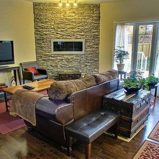 Mittelgroßes, Abgetrenntes Klassisches Wohnzimmer mit beiger Wandfarbe, dunklem Holzboden, Gaskamin, Kaminsims aus Stein, freistehendem TV und braunem Boden in San Diego