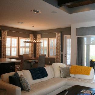 Ispirazione per un grande soggiorno chic aperto con pareti grigie, pavimento in travertino, nessun camino e TV autoportante