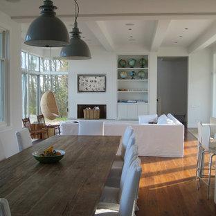 Imagen de salón abierto, costero, con suelo de madera en tonos medios, paredes blancas, marco de chimenea de yeso, televisor retractable y suelo marrón