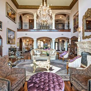 Esempio di un ampio soggiorno mediterraneo aperto con sala formale, parquet scuro, pareti viola, camino classico, cornice del camino in pietra, nessuna TV e pavimento marrone