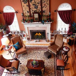 Exemple d'un grand salon chic ouvert avec un mur orange, un sol en bois brun, une cheminée standard, un manteau de cheminée en pierre et aucun téléviseur.