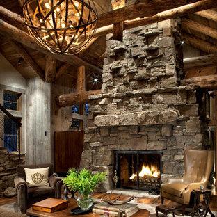Rustikales Wohnzimmer mit Kaminumrandung aus Stein, braunem Holzboden und Kamin in Atlanta