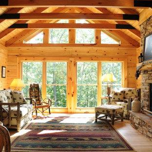 Diseño de salón para visitas cerrado, rústico, de tamaño medio, con marco de chimenea de piedra, paredes marrones, suelo de madera clara y chimenea de doble cara
