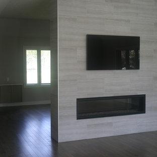 Ispirazione per un grande soggiorno minimalista aperto con sala formale, pareti grigie, pavimento in legno massello medio, camino bifacciale, cornice del camino piastrellata e TV a parete