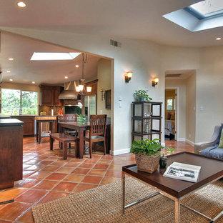 Modelo de salón abierto, de estilo americano, pequeño, con paredes beige, suelo de baldosas de terracota, chimenea tradicional, marco de chimenea de piedra y televisor colgado en la pared