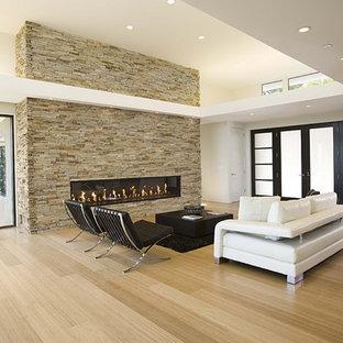 Idee per un soggiorno moderno con camino lineare Ribbon, cornice del camino in pietra e pavimento in bambù