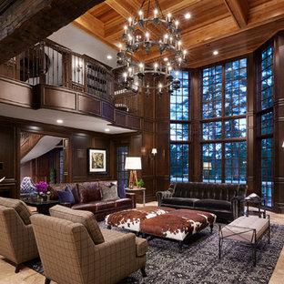 ミネアポリスの巨大なトラディショナルスタイルのおしゃれなリビングロフト (茶色い壁、標準型暖炉、石材の暖炉まわり、埋込式メディアウォール、ベージュの床、フォーマル、ライムストーンの床) の写真