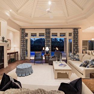 マイアミの大きいトロピカルスタイルのおしゃれなLDK (ベージュの壁、淡色無垢フローリング、横長型暖炉、タイルの暖炉まわり) の写真
