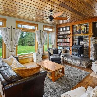 Modelo de salón abierto, rural, extra grande, con paredes multicolor, suelo de madera clara, estufa de leña, marco de chimenea de piedra y suelo marrón