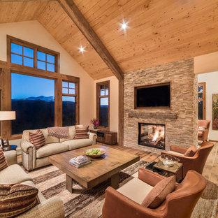 Foto på ett mellanstort rustikt allrum med öppen planlösning, med beige väggar, ljust trägolv, en dubbelsidig öppen spis, en spiselkrans i sten, en väggmonterad TV, ett finrum och beiget golv