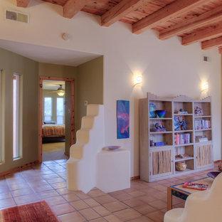 アルバカーキの中サイズのサンタフェスタイルのおしゃれな独立型リビング (フォーマル、ベージュの壁、テラコッタタイルの床、暖炉なし、テレビなし、オレンジの床) の写真