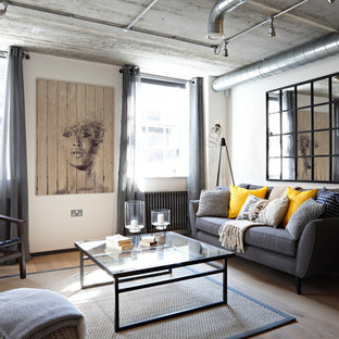 Design ideas for an industrial living room in London with white walls, no fireplace, no tv and light hardwood floors.