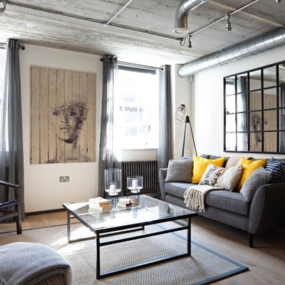 Living room - mid-sized industrial enclosed medium tone wood floor living room idea in London with no fireplace, no tv and white walls