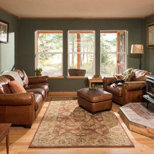Foto de salón abierto, rural, pequeño, con paredes verdes, suelo de madera clara, estufa de leña y marco de chimenea de ladrillo