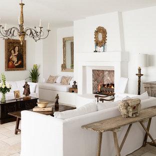 Foto di un grande soggiorno mediterraneo chiuso con sala formale, pareti bianche, pavimento in pietra calcarea, camino classico, cornice del camino in intonaco e nessuna TV