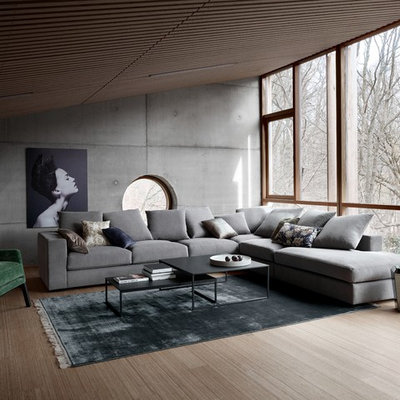 Example of a large urban open concept medium tone wood floor living room design in Manchester with gray walls