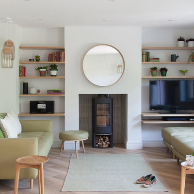 Living room - scandinavian formal and enclosed light wood floor and beige floor living room idea in Cambridgeshire with a wood stove and a tv stand