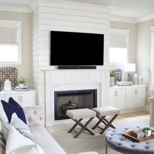 Cette photo montre un grand salon tendance ouvert avec un mur beige, un sol en bois clair, une cheminée standard, un manteau de cheminée en lambris de bois, un téléviseur fixé au mur et un sol beige.