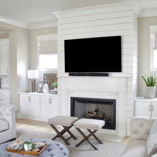 Immagine di un grande soggiorno contemporaneo aperto con pareti beige, parquet chiaro, camino classico, cornice del camino in perlinato, TV a parete e pavimento beige