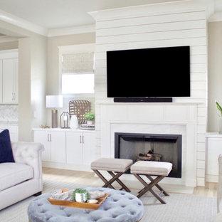 Diseño de salón machihembrado y abierto, actual, grande, con paredes beige, suelo de madera clara, chimenea tradicional, televisor colgado en la pared y suelo beige
