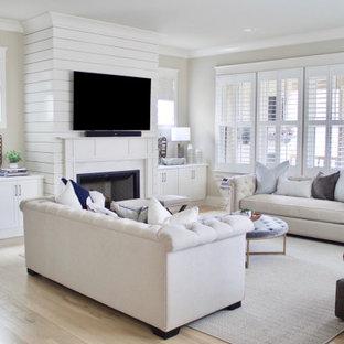 Großes, Offenes Modernes Wohnzimmer mit beiger Wandfarbe, hellem Holzboden, Kamin, Kaminumrandung aus Holzdielen, Wand-TV und beigem Boden in Nashville