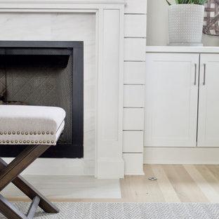 Aménagement d'un grand salon contemporain ouvert avec un mur beige, un sol en bois clair, une cheminée standard, un manteau de cheminée en lambris de bois, un téléviseur fixé au mur et un sol beige.