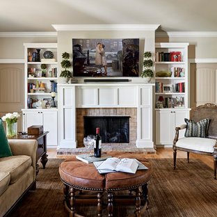 Inspiration for a transitional medium tone wood floor and brown floor living room remodel in Nashville with a standard fireplace, a wall-mounted tv, beige walls and a brick fireplace