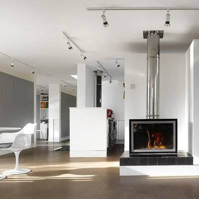 Example of a large trendy open concept concrete floor living room design in London with a wood stove