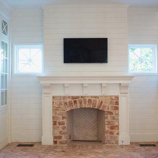 Diseño de salón para visitas cerrado, clásico, de tamaño medio, con paredes blancas, suelo de ladrillo, chimenea tradicional, marco de chimenea de ladrillo, televisor colgado en la pared y suelo rosa