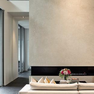Immagine di un soggiorno moderno con pareti bianche, pavimento con piastrelle in ceramica, camino lineare Ribbon, cornice del camino in cemento e pavimento nero