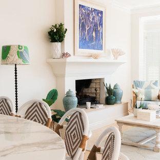 Esempio di un grande soggiorno mediterraneo aperto con sala formale, pareti bianche, pavimento in pietra calcarea, camino classico, cornice del camino in cemento e TV autoportante