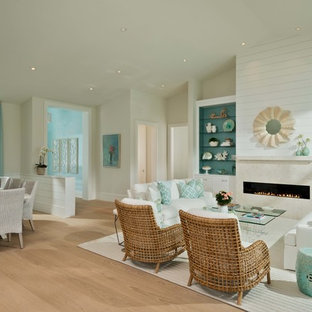Beach style formal open concept living room in Miami with beige walls, light hardwood floors, a ribbon fireplace, a stone fireplace surround, no tv and beige floor.