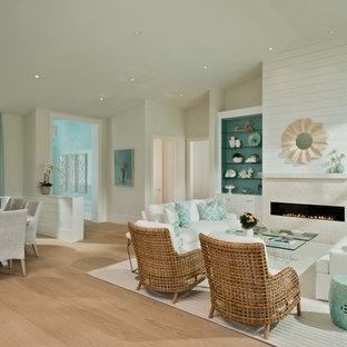 マイアミのビーチスタイルのおしゃれなLDK (フォーマル、ベージュの壁、淡色無垢フローリング、横長型暖炉、石材の暖炉まわり、テレビなし、ベージュの床) の写真