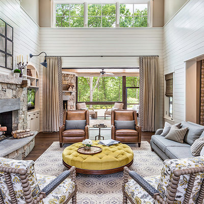 Inspiration for a large farmhouse open concept medium tone wood floor and brown floor living room remodel in Other with white walls, a standard fireplace, a stone fireplace and a media wall