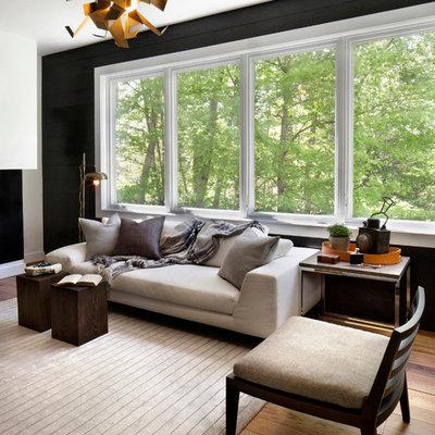 Living room - contemporary medium tone wood floor living room idea in New York with black walls