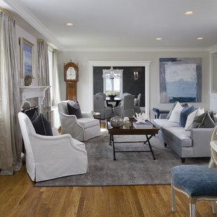 Imagen de salón para visitas cerrado, clásico renovado, de tamaño medio, sin televisor, con paredes grises, suelo de madera en tonos medios, chimenea tradicional y marco de chimenea de piedra