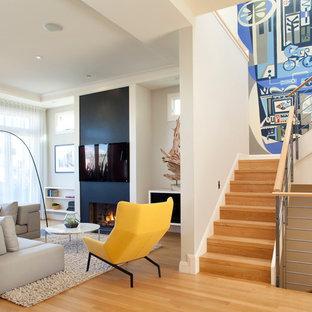 Foto de salón actual con paredes blancas, suelo de madera clara, chimenea tradicional, televisor colgado en la pared y suelo beige