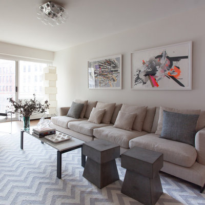 Inspiration for a mid-sized contemporary formal and open concept medium tone wood floor and brown floor living room remodel in New York with white walls, no fireplace and a wall-mounted tv