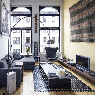Idee per un piccolo soggiorno minimalista con pavimento in legno massello medio, TV autoportante, sala formale, pareti gialle, nessun camino e pavimento marrone