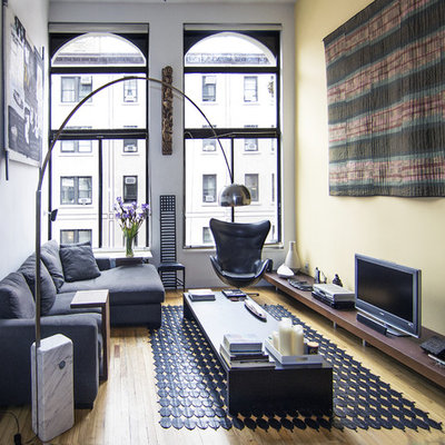 Example of a small minimalist formal medium tone wood floor and brown floor living room design in New York with a tv stand, yellow walls and no fireplace