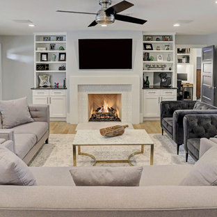 Mid-sized transitional enclosed light wood floor and beige floor living room photo in Houston with gray walls, a standard fireplace and a wall-mounted tv