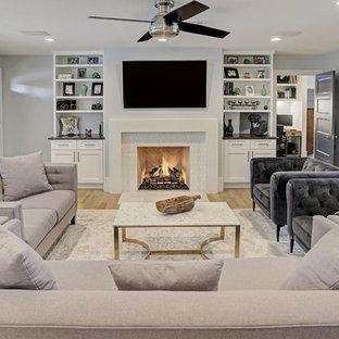 ヒューストンの中サイズのトランジショナルスタイルのおしゃれな独立型リビング (グレーの壁、淡色無垢フローリング、標準型暖炉、壁掛け型テレビ、ベージュの床) の写真