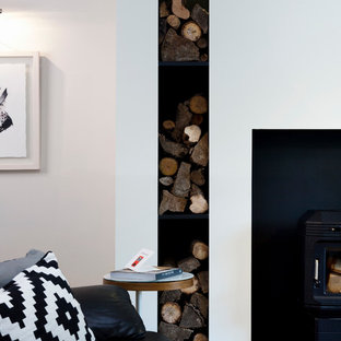 Example of a mid-sized minimalist enclosed living room design in Dublin with white walls, a wood stove and a tv stand