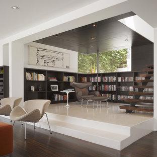 Modelo de biblioteca en casa abierta, moderna, pequeña, con paredes blancas y suelo de madera oscura