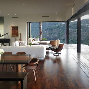 Modelo de salón con rincón musical abierto, moderno, de tamaño medio, sin televisor, con paredes blancas, suelo de madera en tonos medios, chimenea lineal y marco de chimenea de yeso