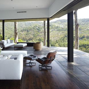 Modelo de salón abierto, minimalista, de tamaño medio, con paredes blancas y suelo de madera oscura